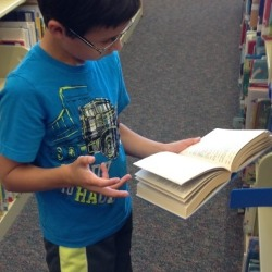 Student actively reading a book in the library